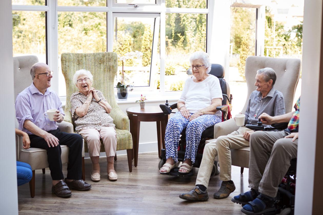 a group of elderly people sitting together smiling and laughin