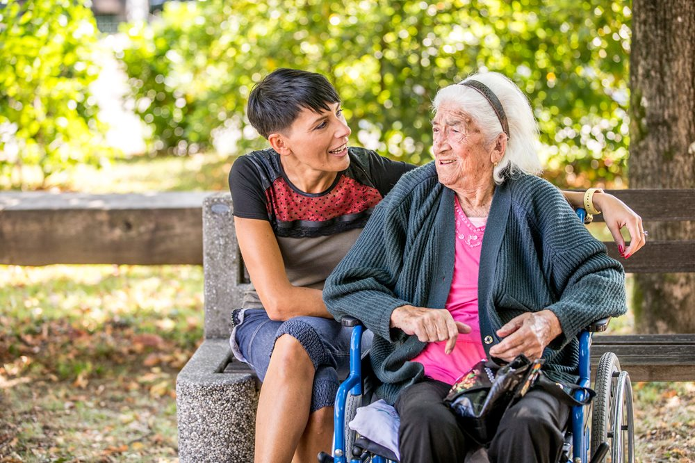Senior woman in wheelchair with a family member who is sitting on a park bench.