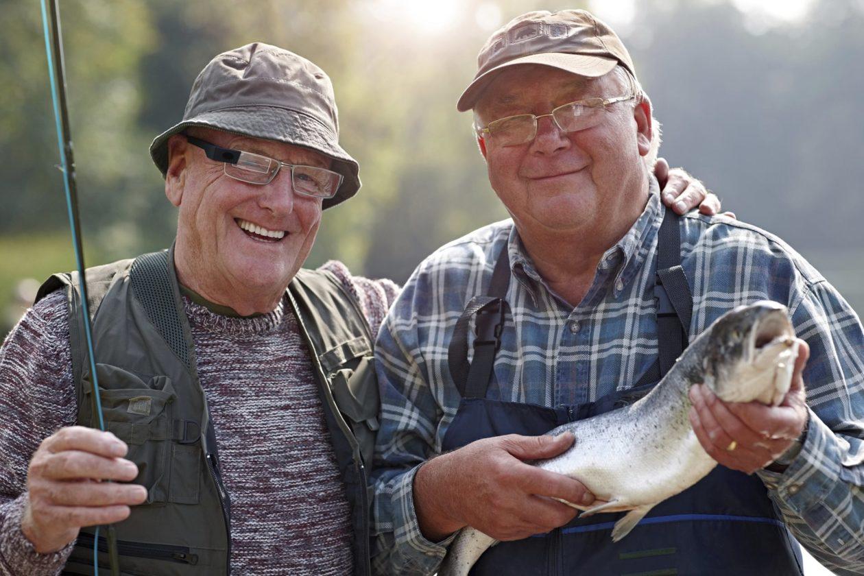 Two fisherman holding fish