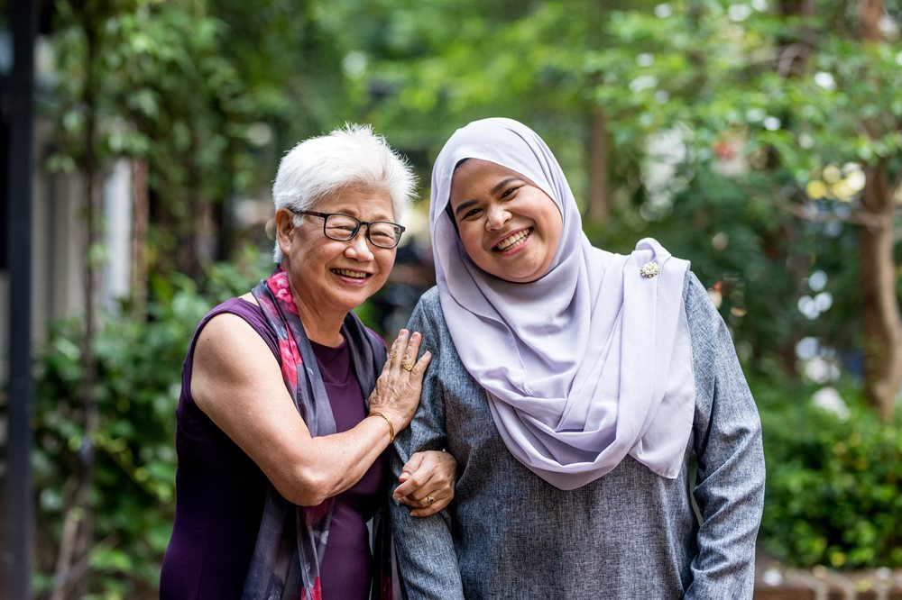 Two ladies of different ages and different cultures smiling.
