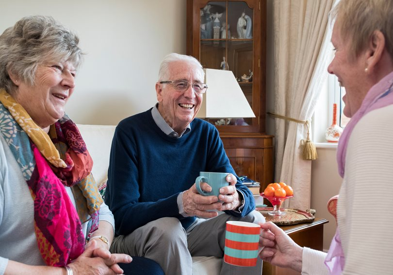 Three people drinking tea and laughing together