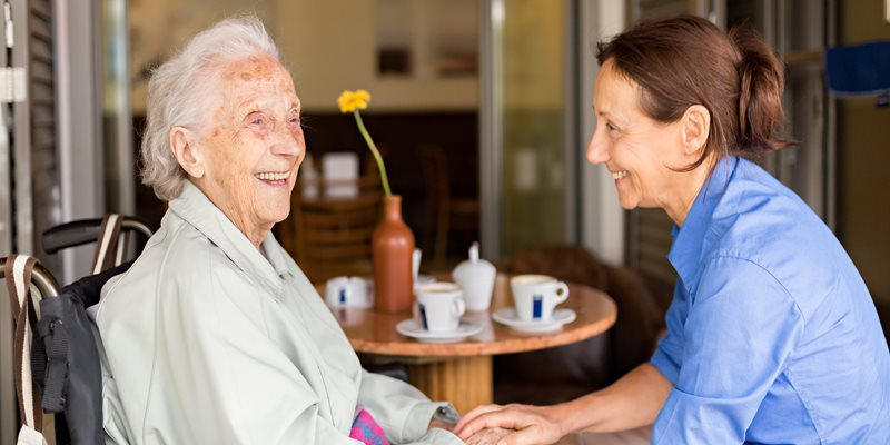 Elderly woman and young woman laughing together