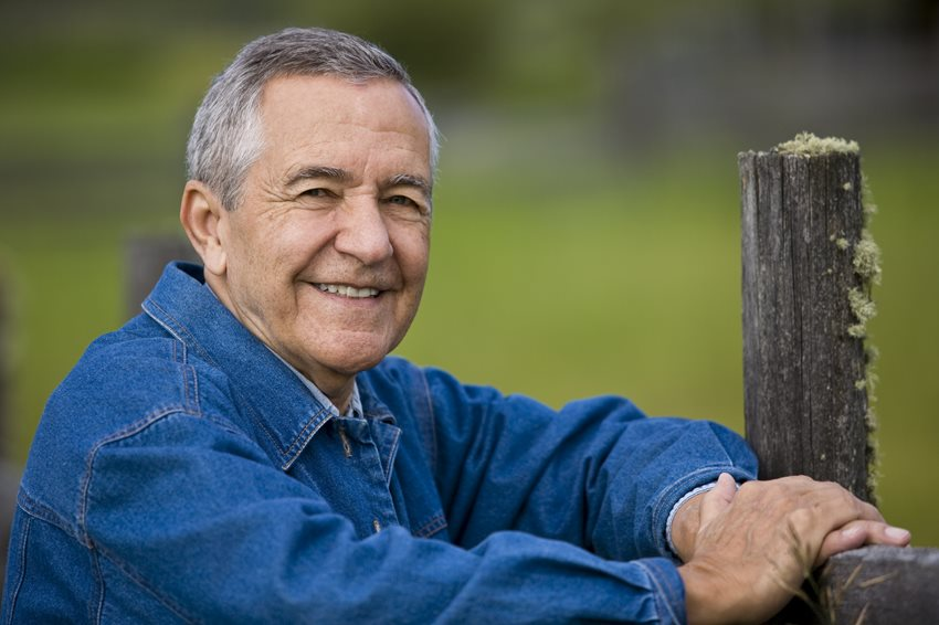 Man leaning on a fence and smiling