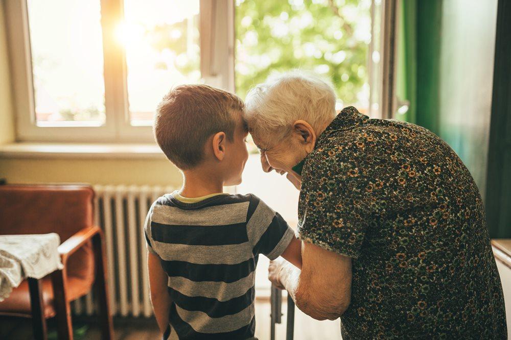 Senior woman bending over and hugging her grandsons arm