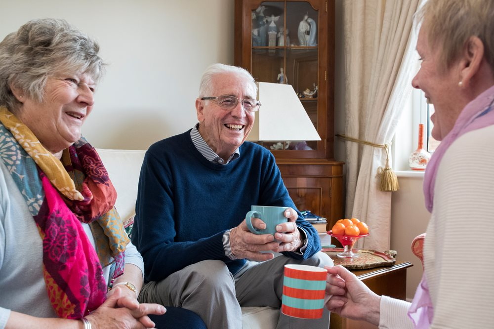 Group of two senior woman and one male drinking tea and laughing.