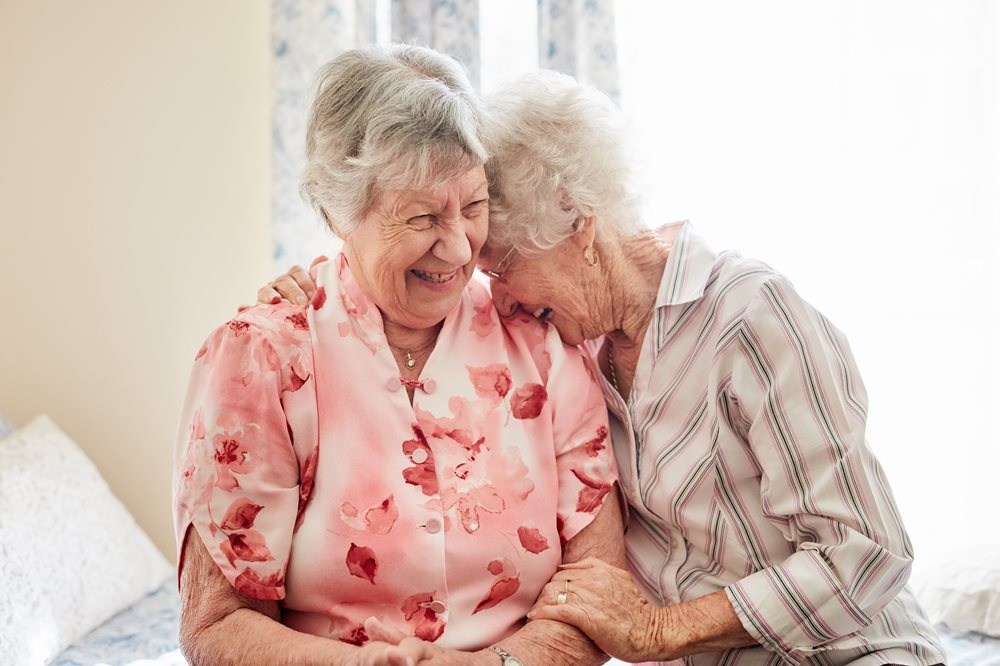 2 senior women laughing together. One is laughing into the other's shoulder.