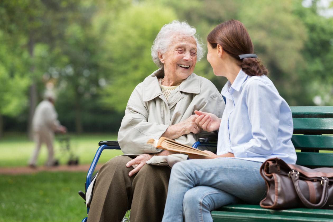Older woman with caregiver sat on park bench smiling