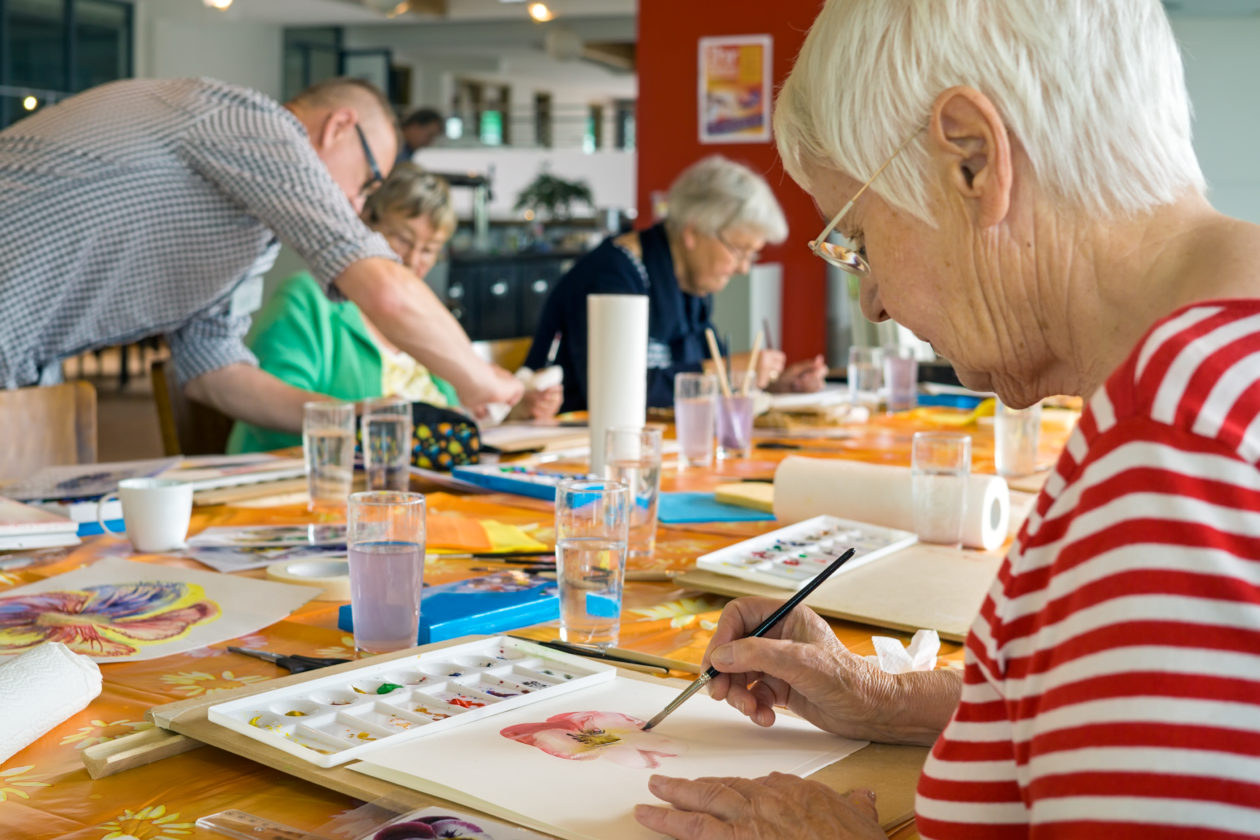 Older person sitting at a table painting with watercolours