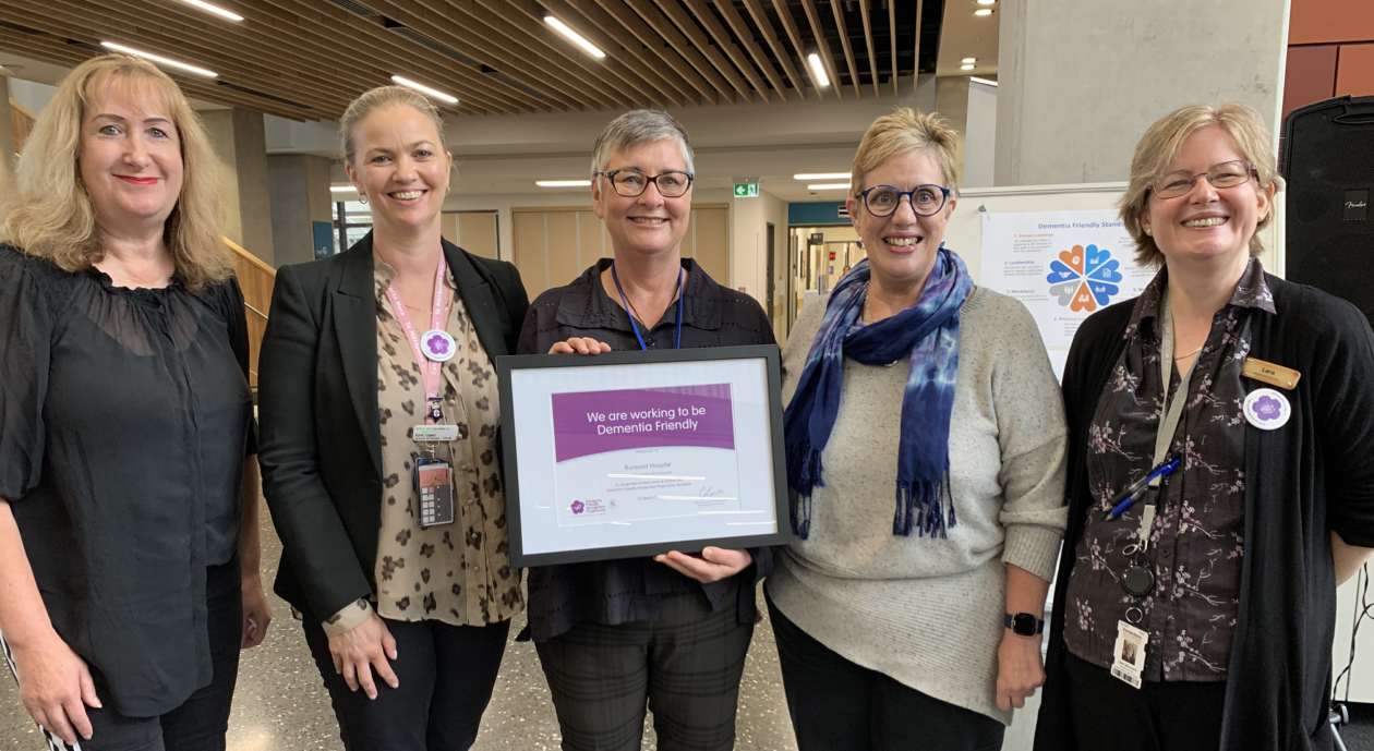 Group of people smiling and receiving the Dementia Friendly certificate