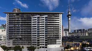 Outside of a hotel with Sky Tower in background