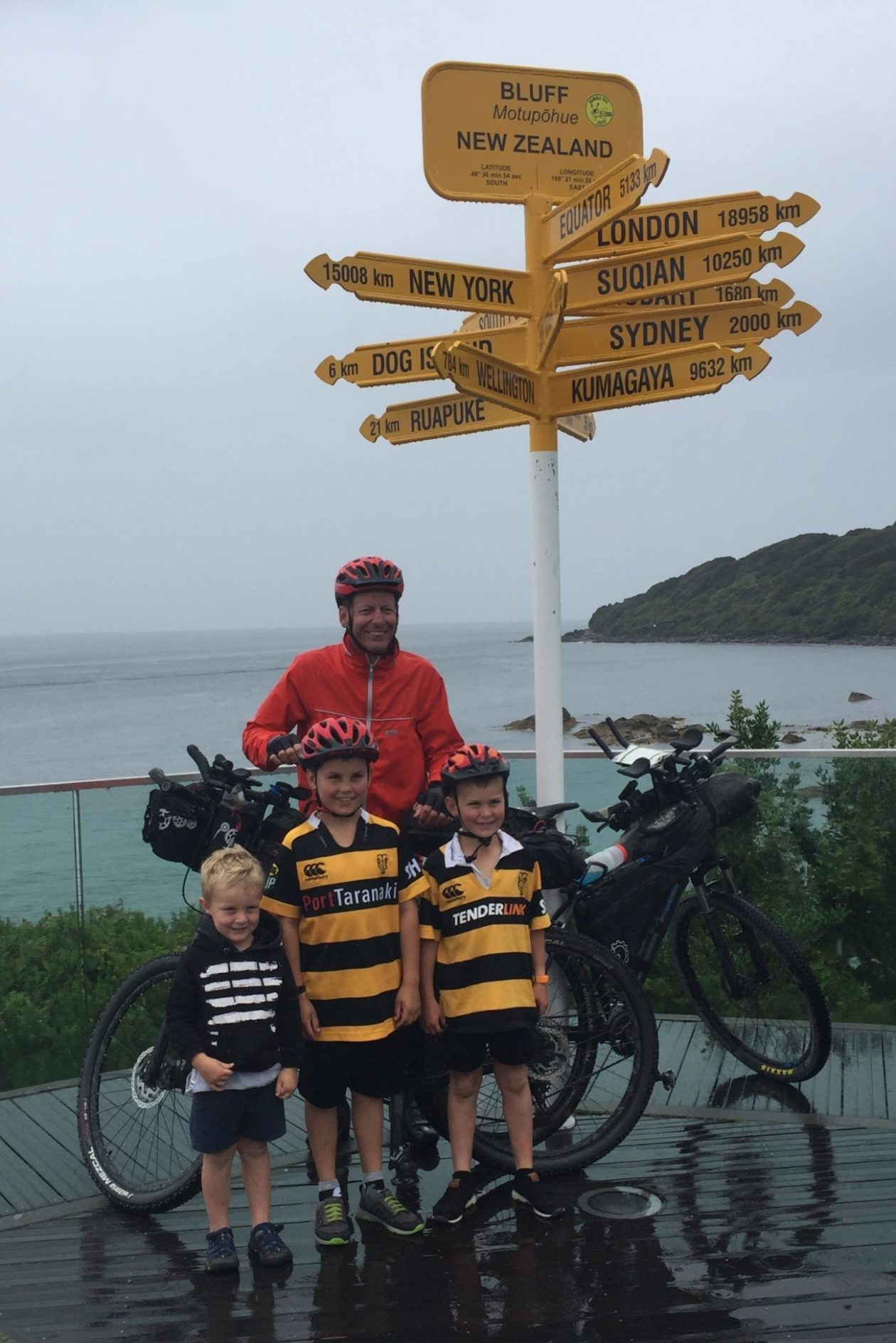 Mark at the Bluff viewpoint with his bike and his nephews smiling in the rain