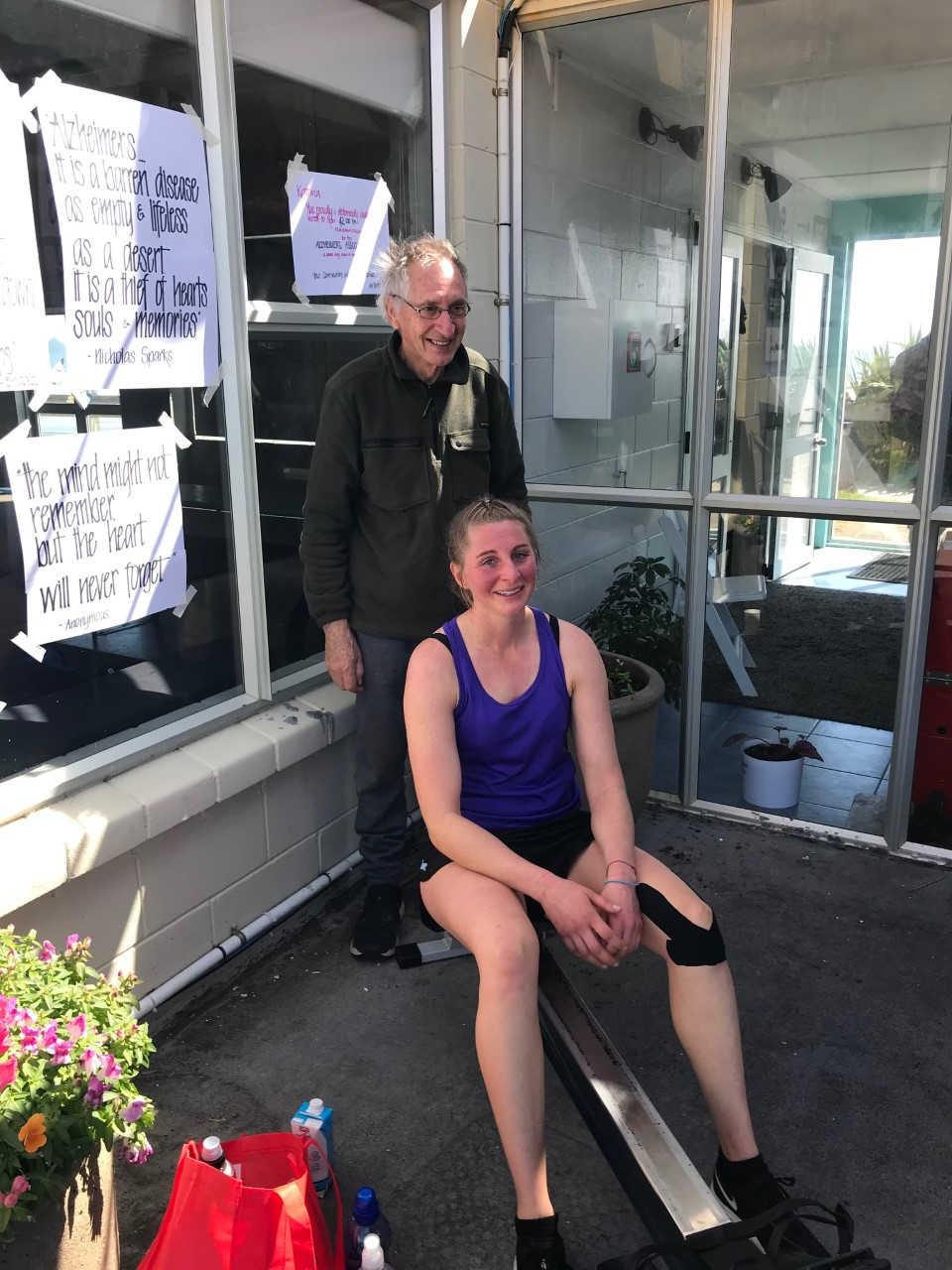 Katrina on the rowing machine with her Dad standing beside her